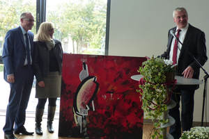 "<div class=""bildtext_en""><span class=""bildnummer"">»3</span> Building planner Karl-Heinz-Herrmann presents Christa and Klaus Schülein with artwork for design of the new offices (right to left)</div>"