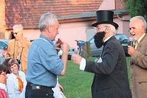 """<span class=""""bildunterschrift_hervorgehoben"""">»4</span> Friedrich E. Hoffmann (Heinz Lachetta) überreicht Dr. Müller ein Präsent (im Hintergrund rechts: Dr. Lothar Schyia)<br />"""