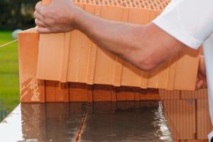 """<div class=""""bildtext_en"""">e) Place next row of bricks on the moist mortar tape</div>"""