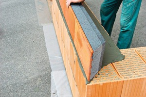 "<div class=""bildtext_en""><span class=""bildnummer"">»3</span> After a layer of mortar or PU foam, the Unipor slab edge element is placed on the clay block wall and aligned</div>"
