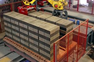 """<div class=""""bildtext""""><span class=""""bildnummer"""">»4</span> Der Roboter setzt die Produkte zu jeweils 5 Paketen in zwei Reihen auf die Ofenwagen </div>"""