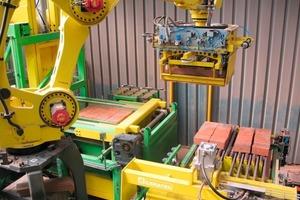 &gt;&gt;1 Ein Roboter setzt die lagenweise sortierten Ziegel auf eine Hebebühne<br />