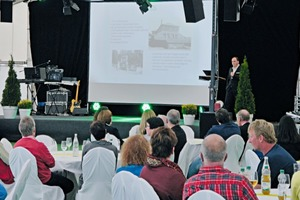 "<div class=""bildtext_en"">»1 Dipl.-Ing. (FH) Kai Rudhof telling the guests about the company's 80-year history</div>"