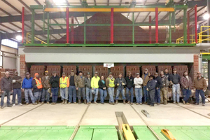 """<div class=""""bildtext_en""""><span class=""""bildnummer"""">»4</span> """"First Brick out"""" in January 2016 – as the team looks on with pride while the first bricks emerge from the kiln </div>"""